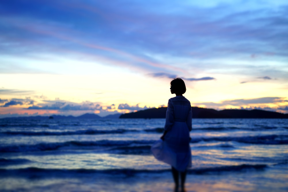 silhouette photography of woman standing on shore during golden hour