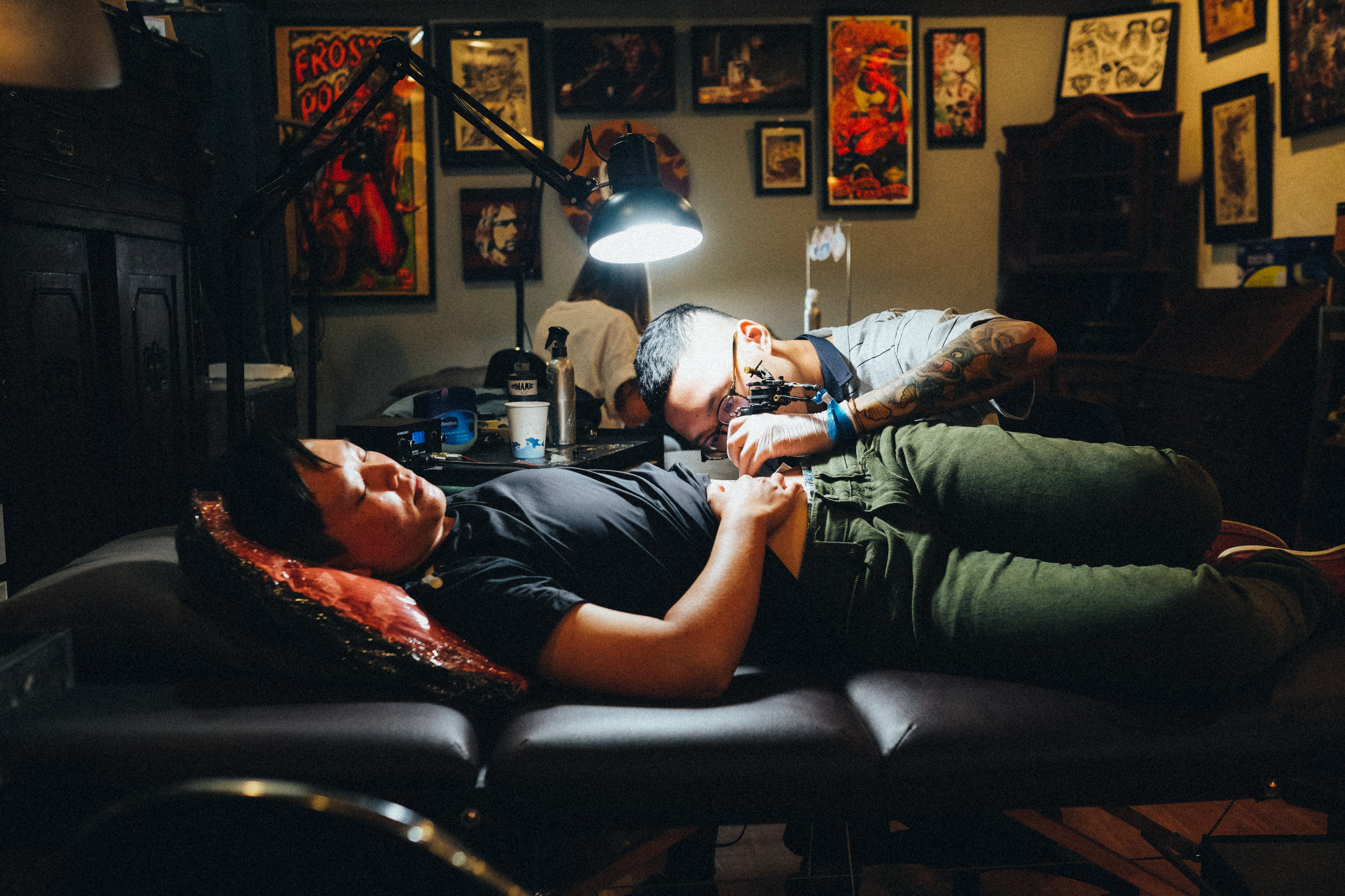man in gray polo shirt tattooing a man
