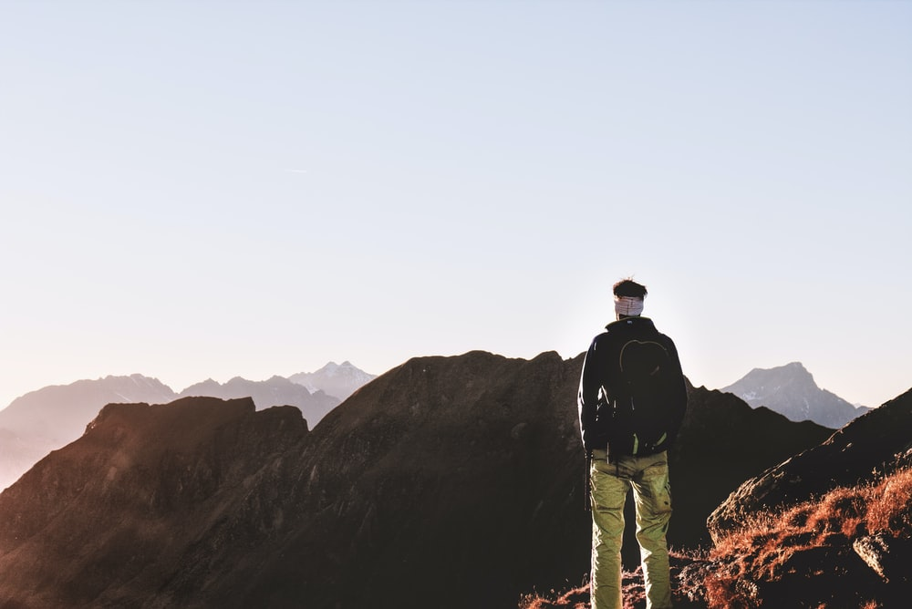 man standing in front of brown mountain scenery during daytime