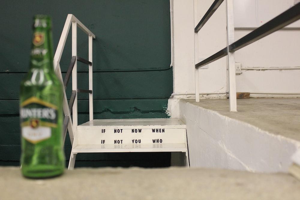 green glass bottle standing near gray concrete stair