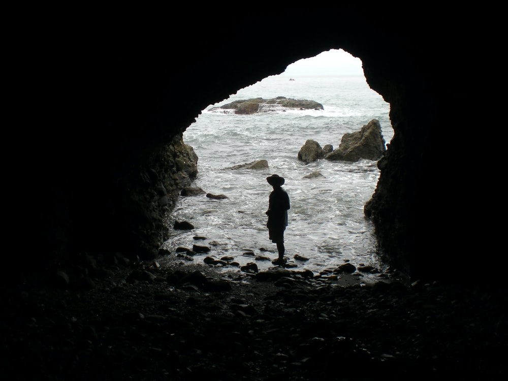 silhouette of person wearing hat taking picture inside cave near sea water