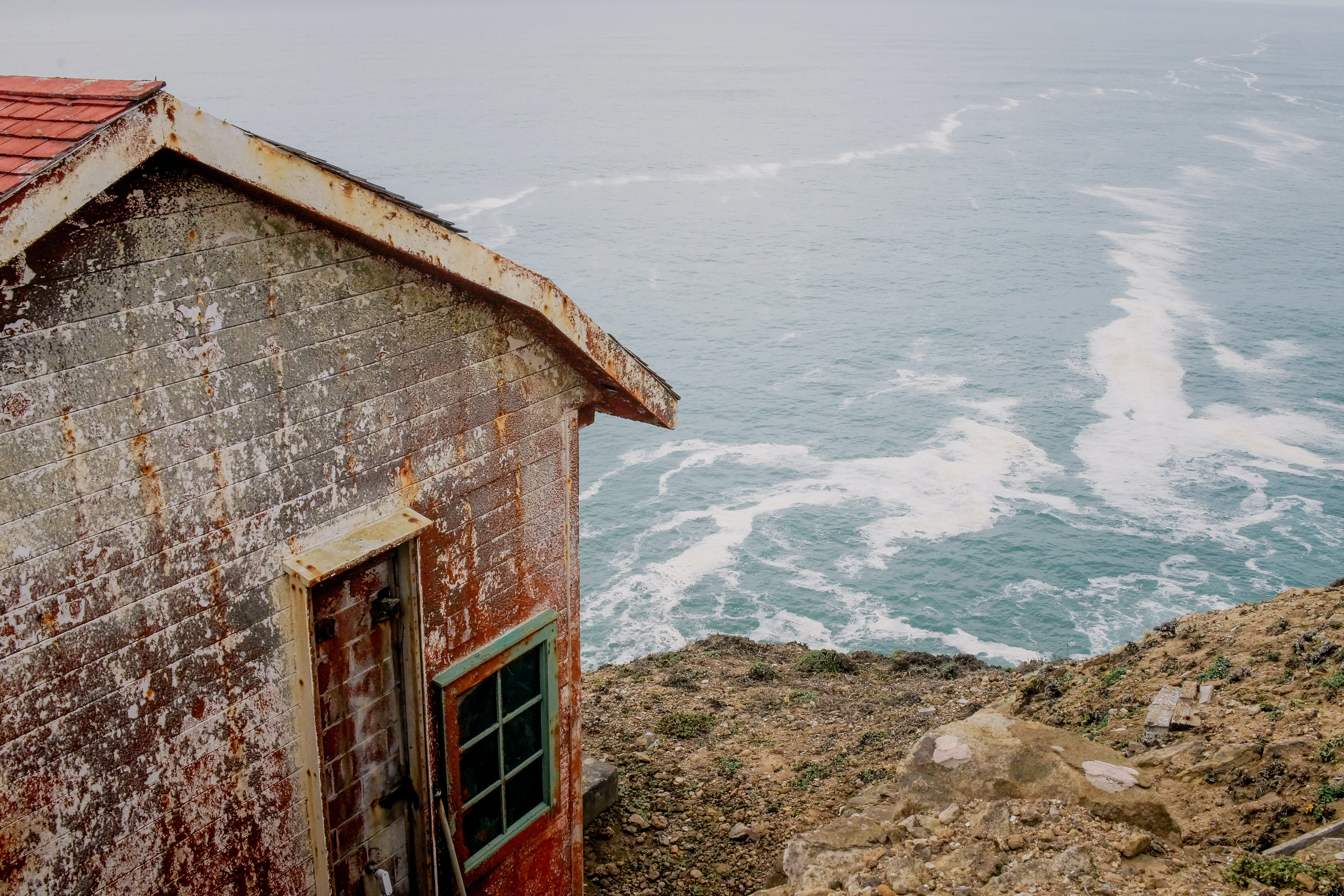 gray and red concrete house near the body of water