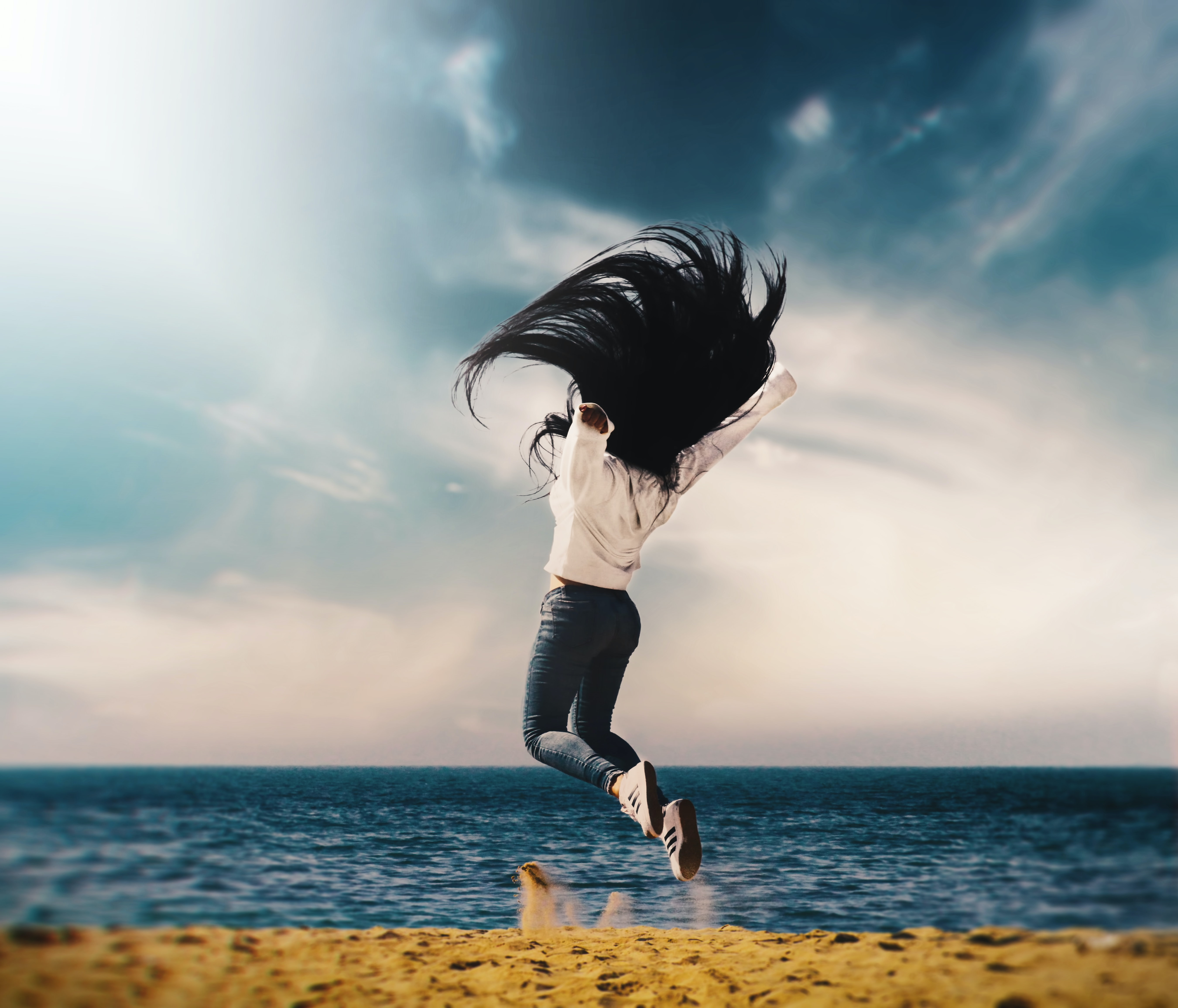 woman in white long-sleeved shirt and blue jeans jumping on seashore during daytime