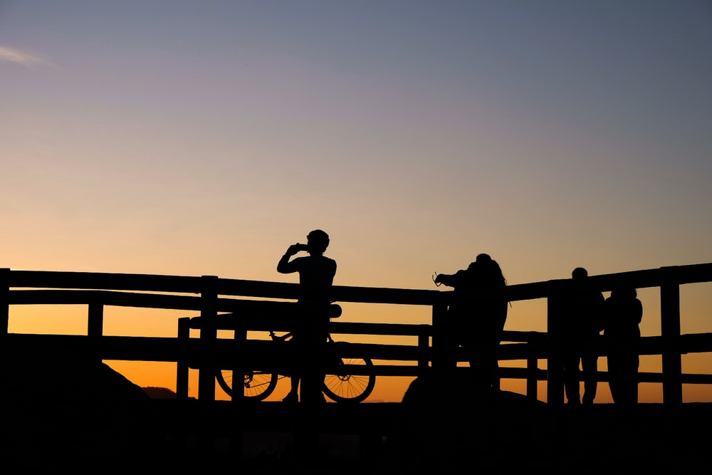 silhouette photo of persons taking photo of sunset