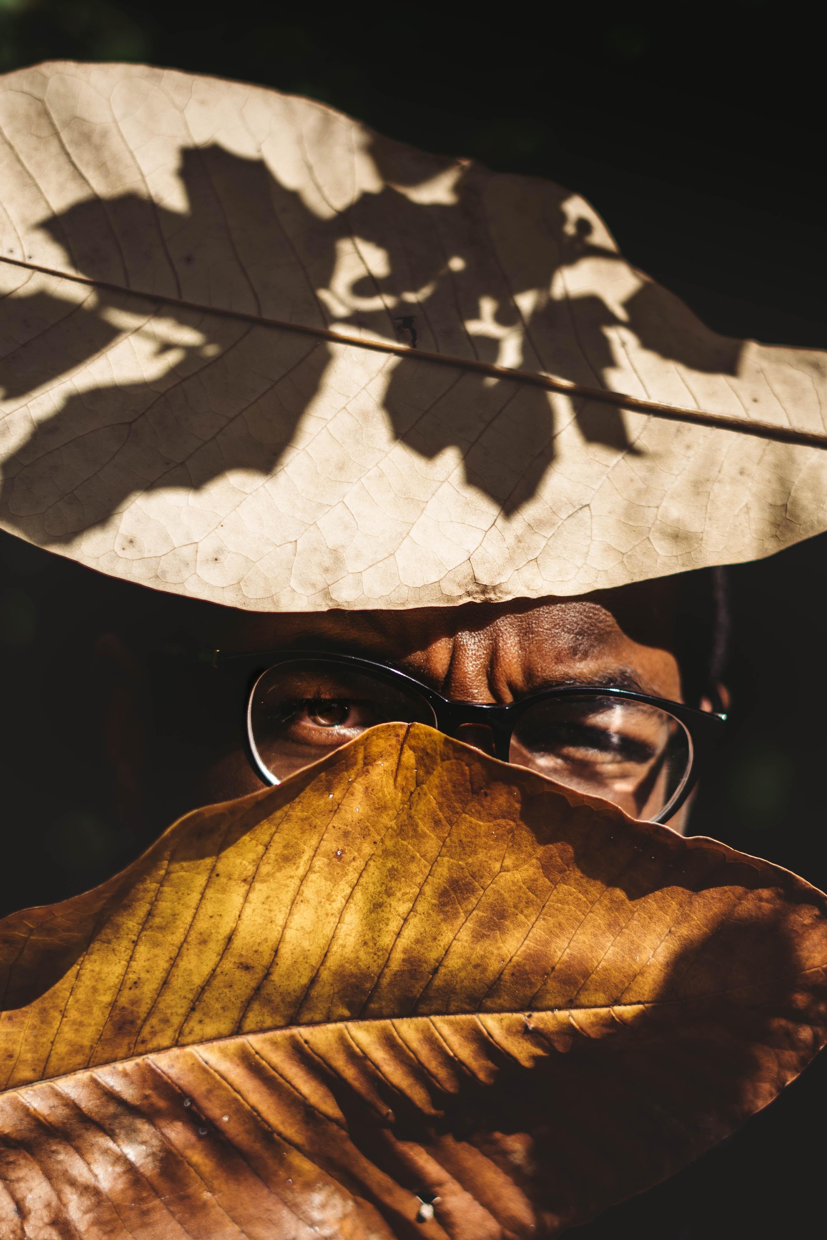 person wearing eyeglasses between brown leaves