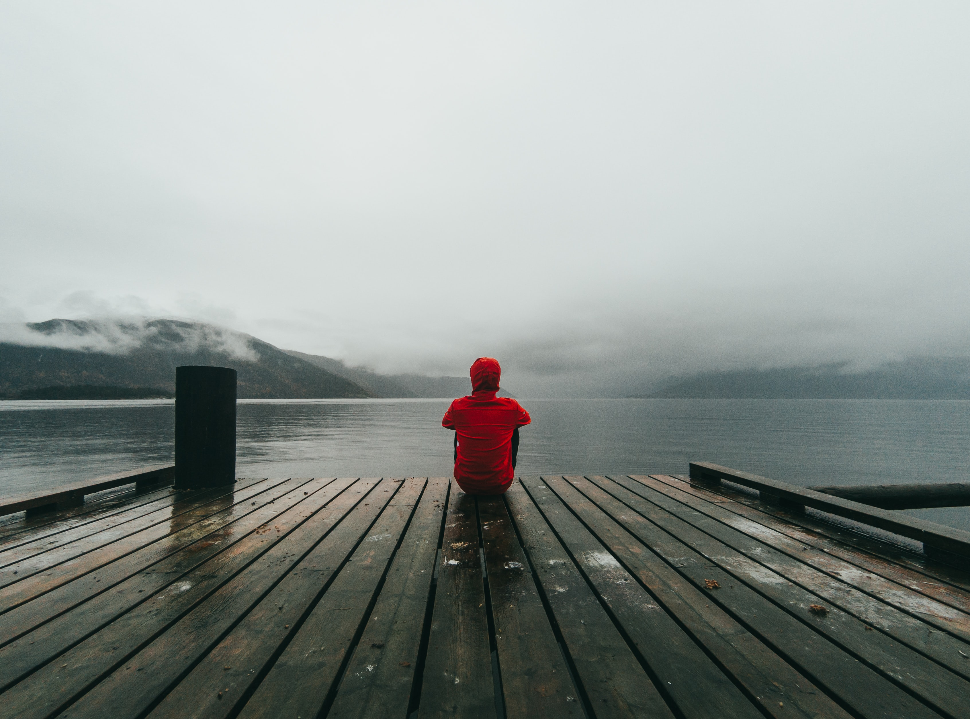 person wearing red hooded jacket sitting on brown and black wooden sea dock near mountains under gray sky during daytime
