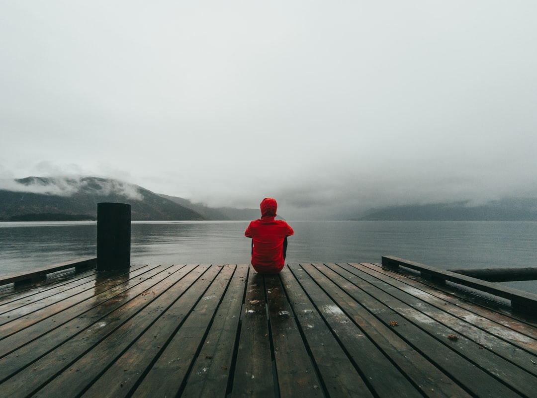 Person in red hoodie sitting at the end of a dock