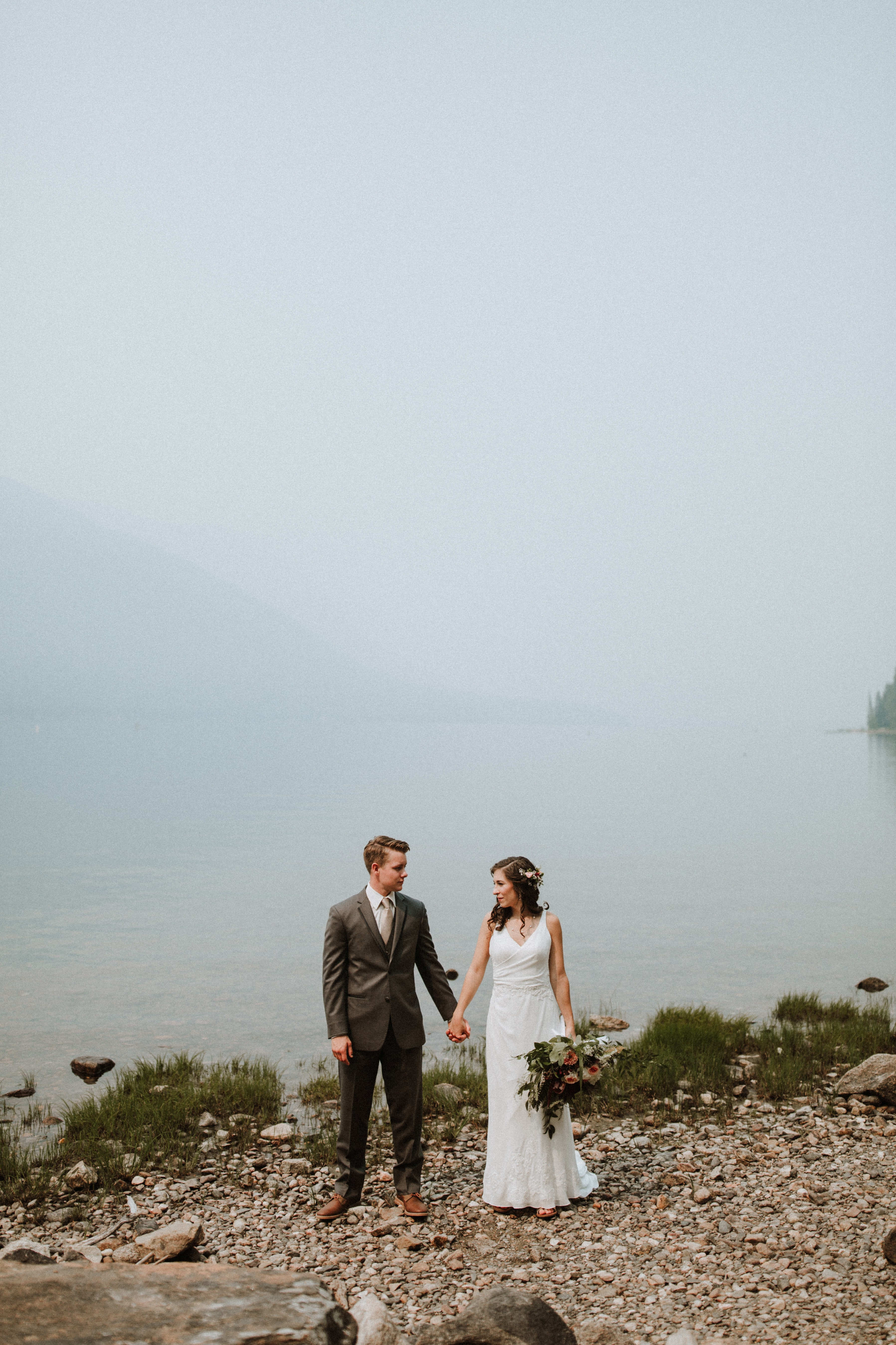 wedding couple standing beside body of water near mountain under white sky during daytime