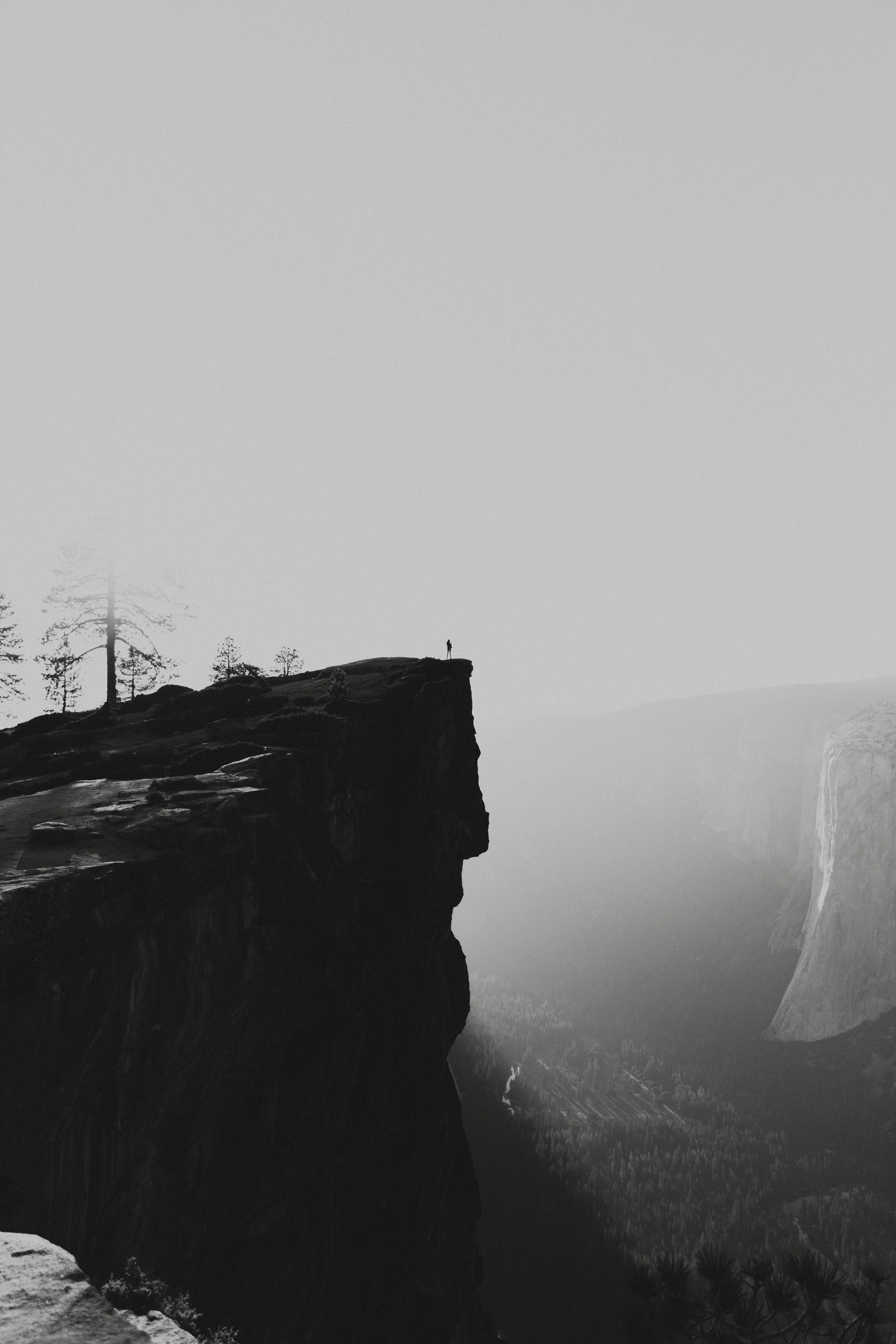 human standing on brown cliff