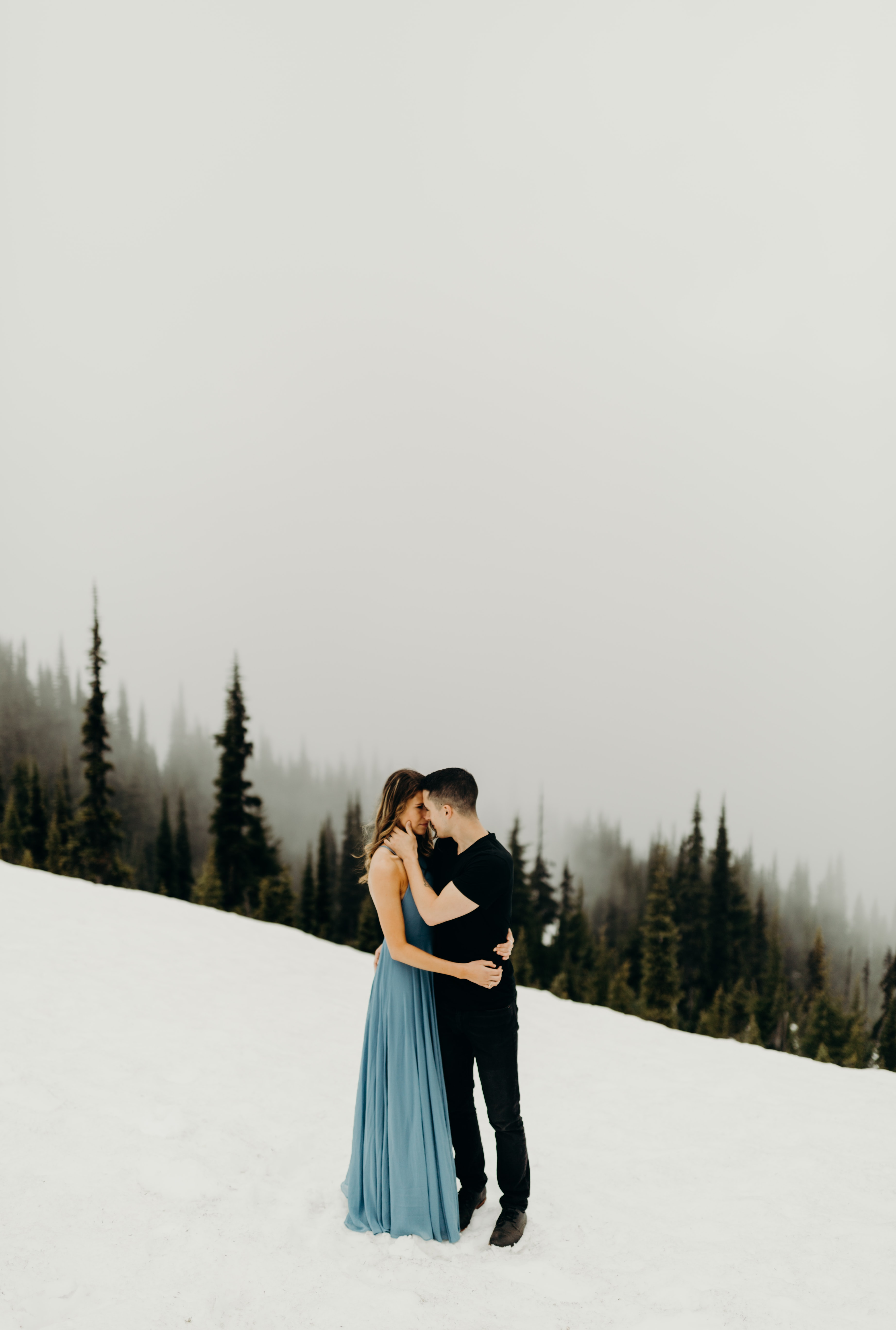 woman in teal dress and man in black shirt performing kiss on top of snowy mountain during daytime