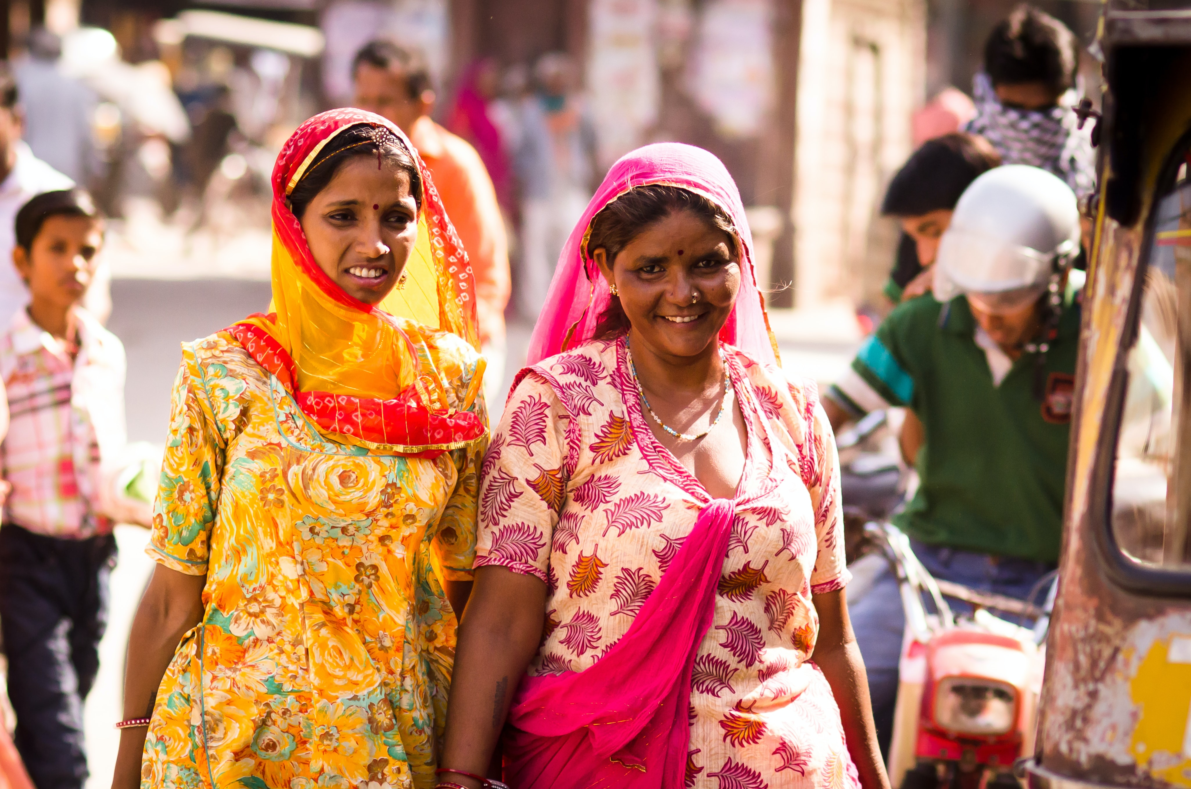 two women wearing traditional dress walking on street while smiling during daytime