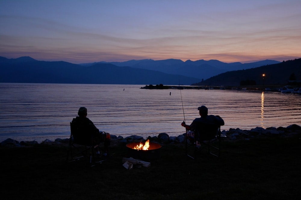 silhouette of two men next to calm body of water