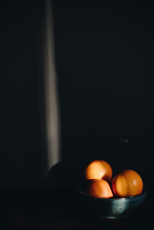 three orange citrus fruits with bowl