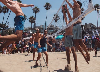 group of men playing beach volleyball