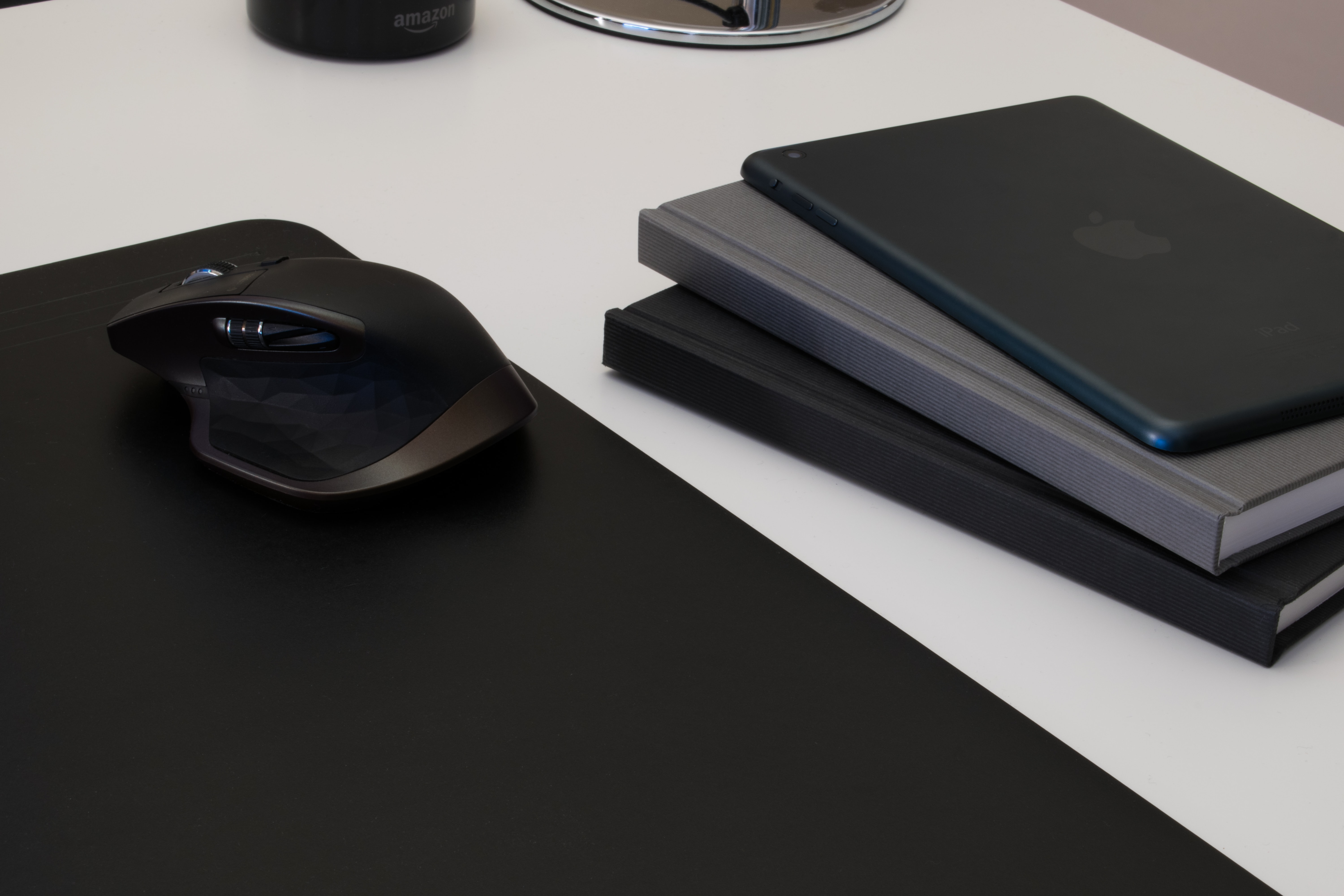 black and gray cordless mouse on black mousepad near black and gray books