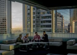 four men drinking on sofa