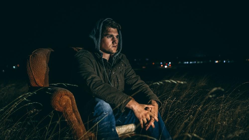 man in brown full-zip jacket sitting on brown suede armchair