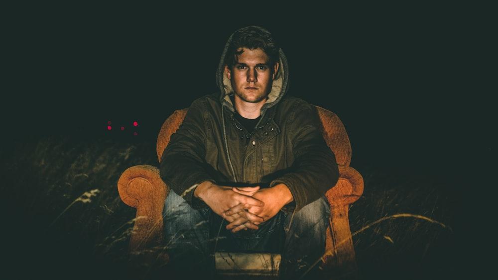man wearing black zip-up hooded jacket sitting on sofa chair
