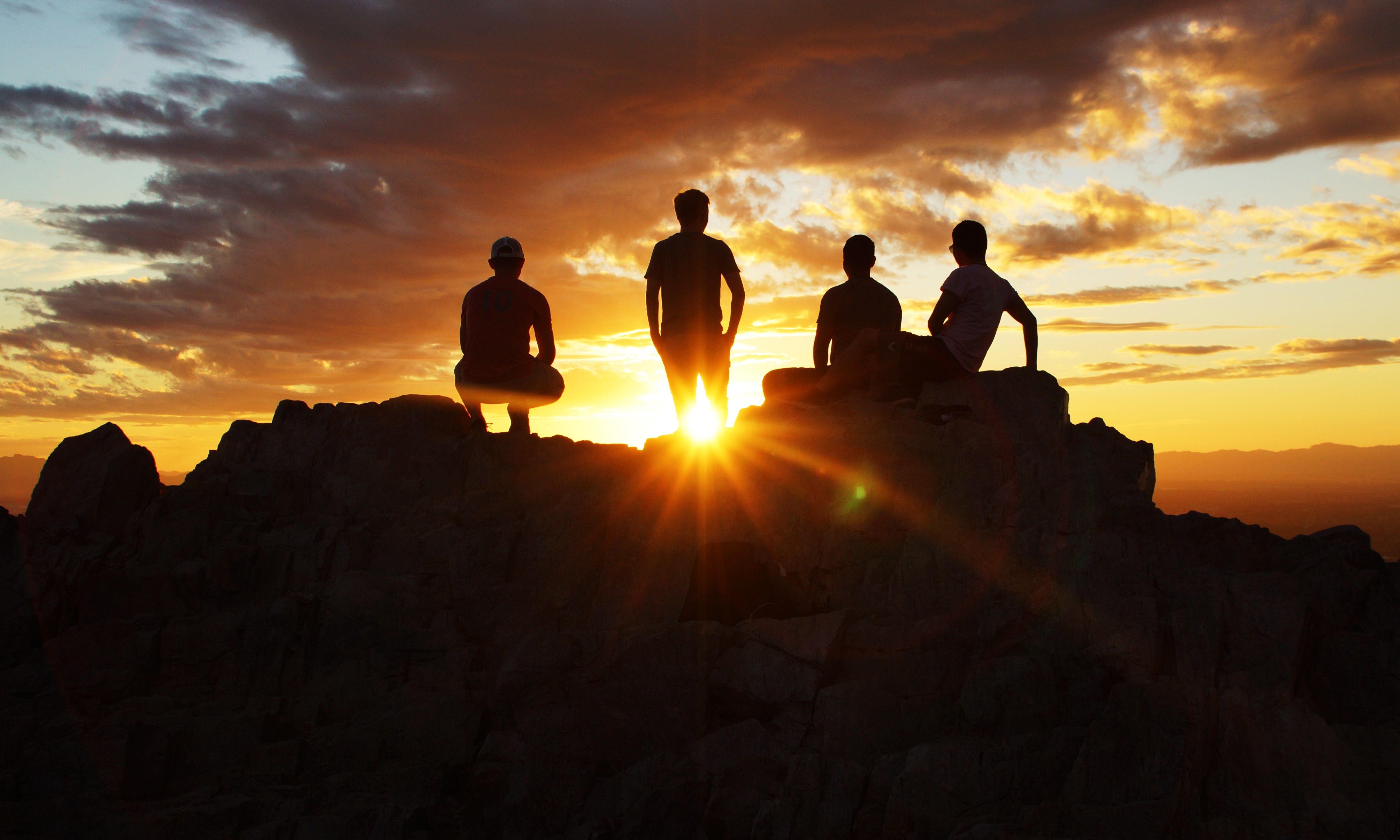 silhouette photography of four person on cliff during sunset