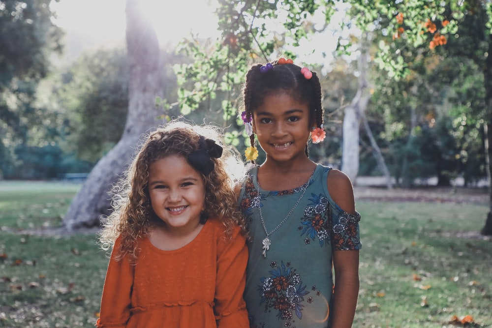 two dressed children standing against trees
