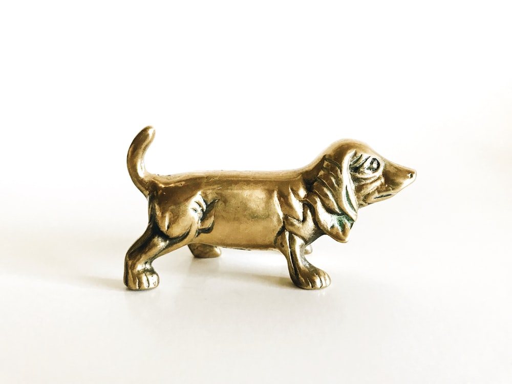 brown wooden dog figurine on white surface
