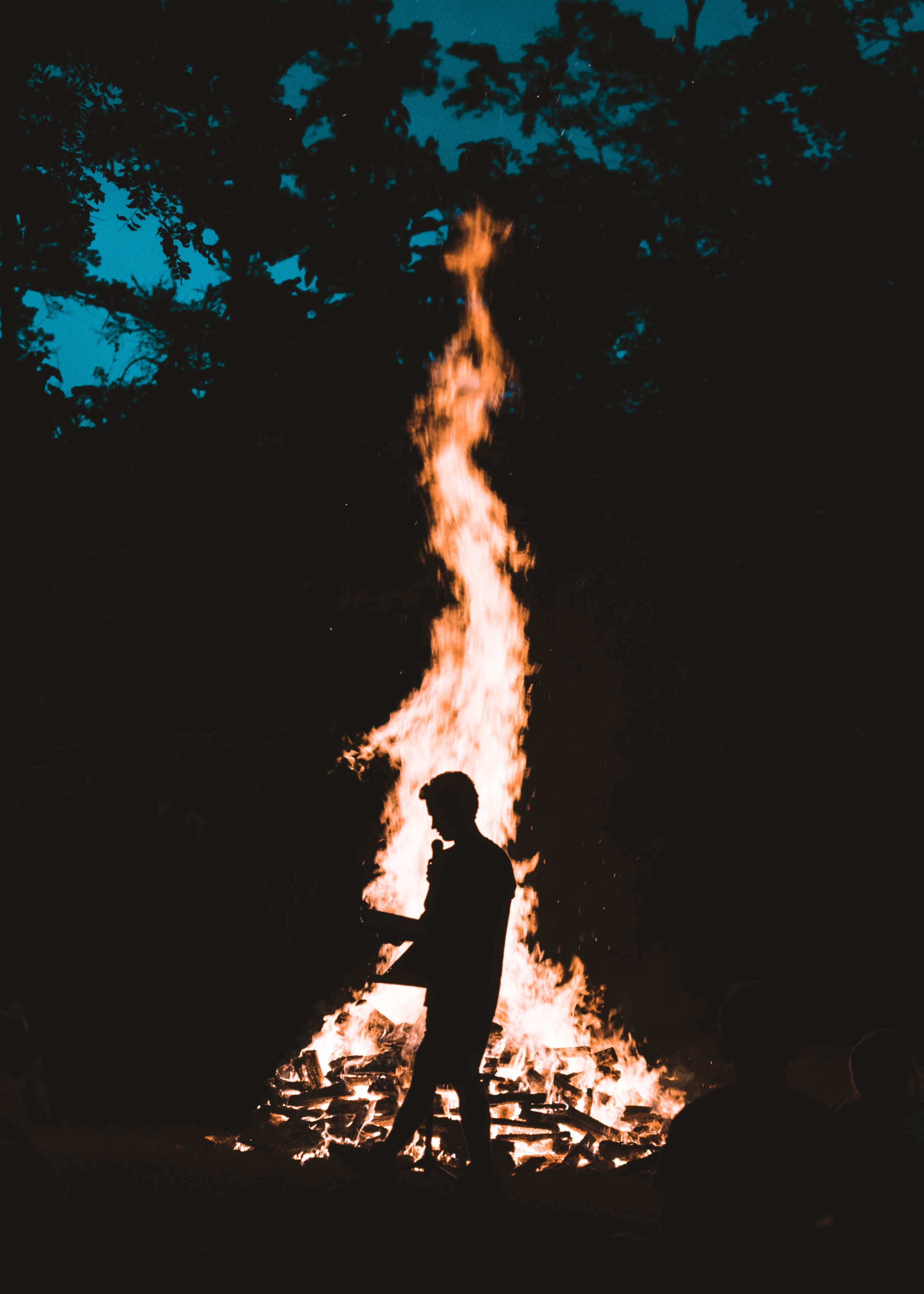 silhouette of man in front of bonfire