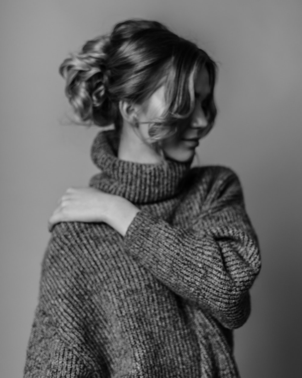 woman wearing turtleneck sweater touching her shoulder with her left hand grayscale photo