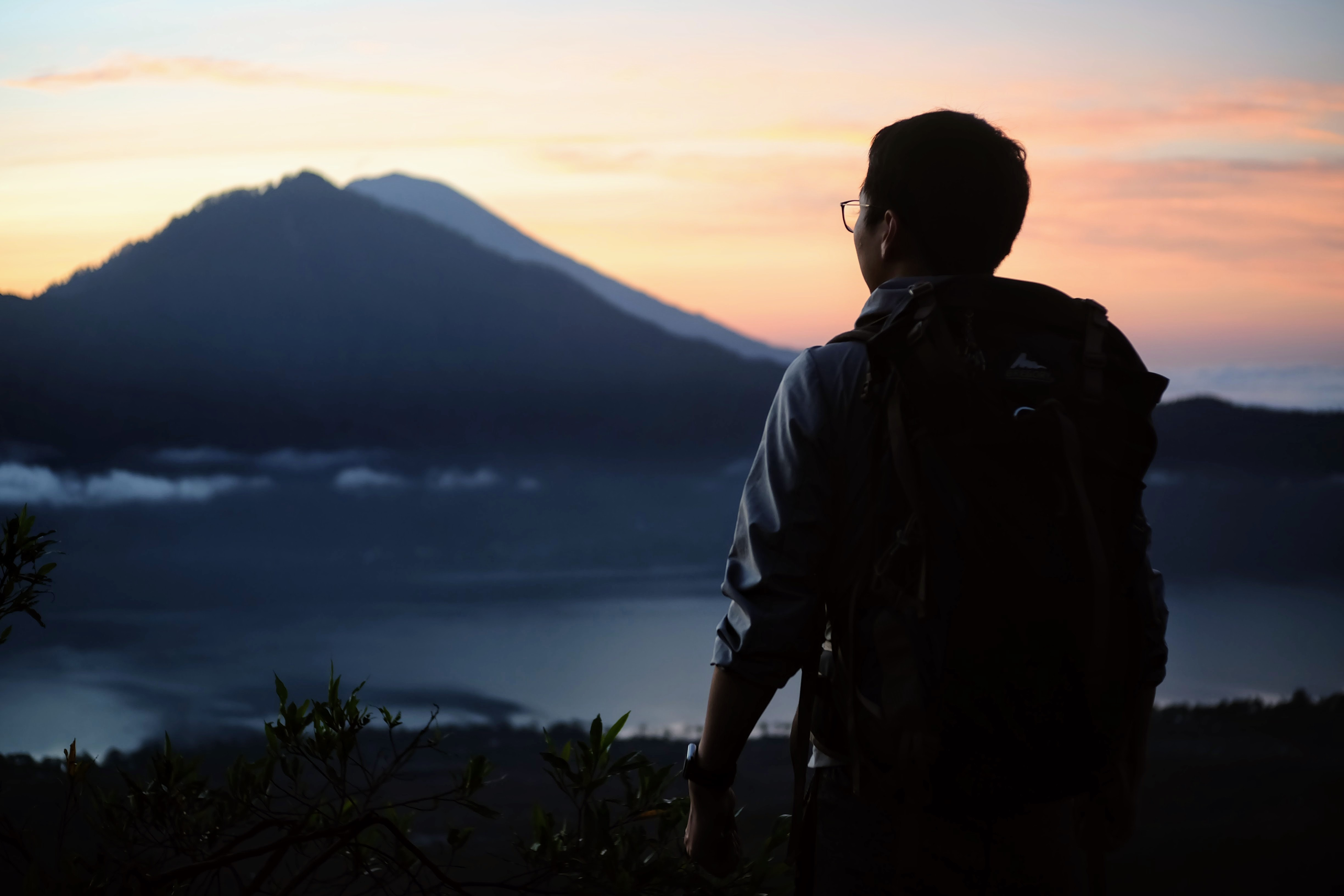 man wearing black backpack standing and watching mountain