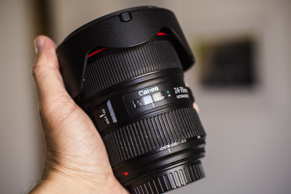 person holding black Canon zoom lens