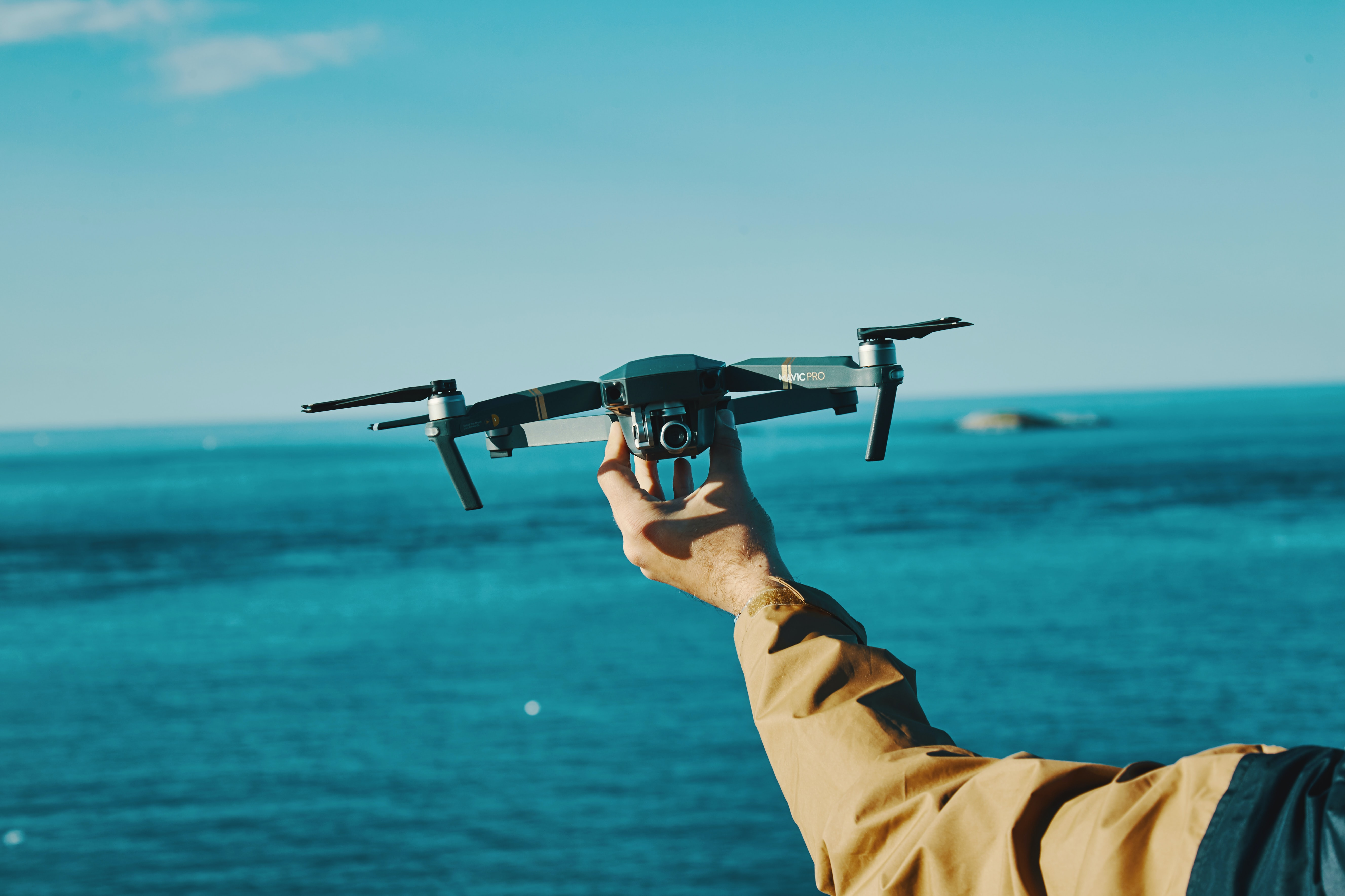 person holding grey drone in front of sea