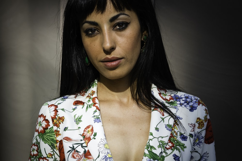 woman wearing white, green, red, and orange floral collared blazer