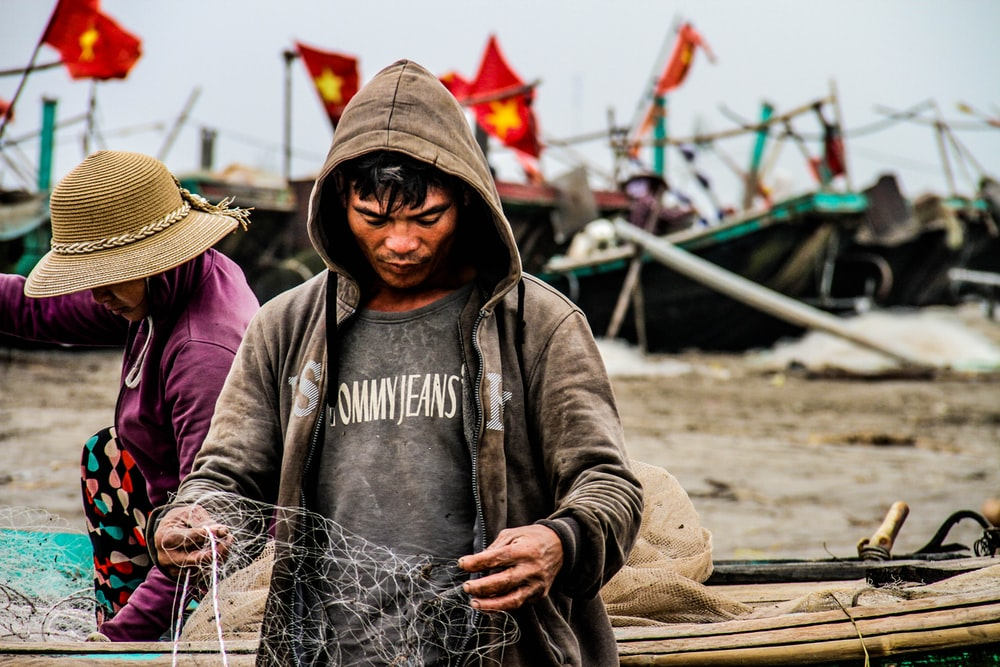 person holding fishing net near brown boat during daytime