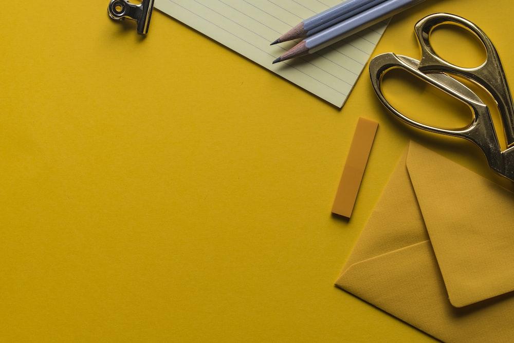 gray scissor with envelope and pencils