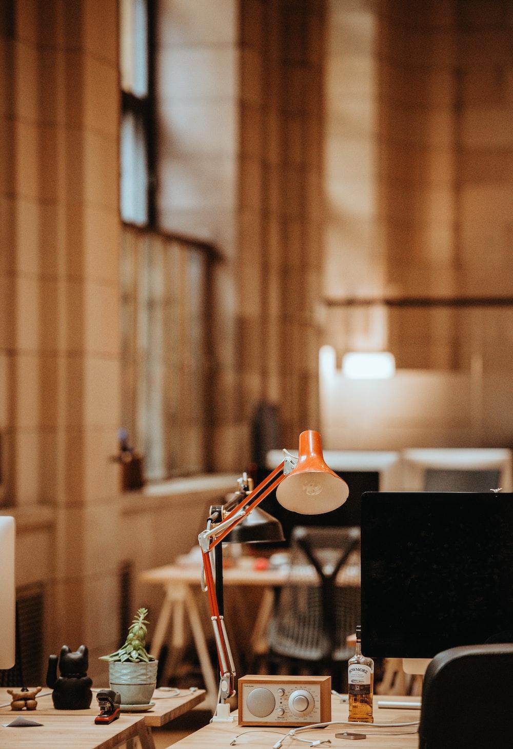 brown desk lamp beside computer monitor on desk