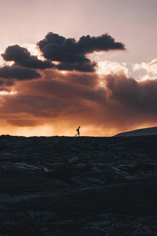 landscape photo of person walking on horizon