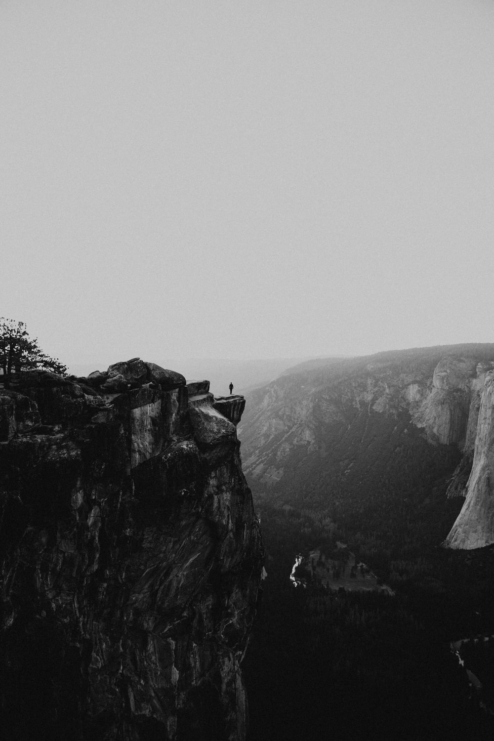 grayscale photo of person standing on mountain cliff