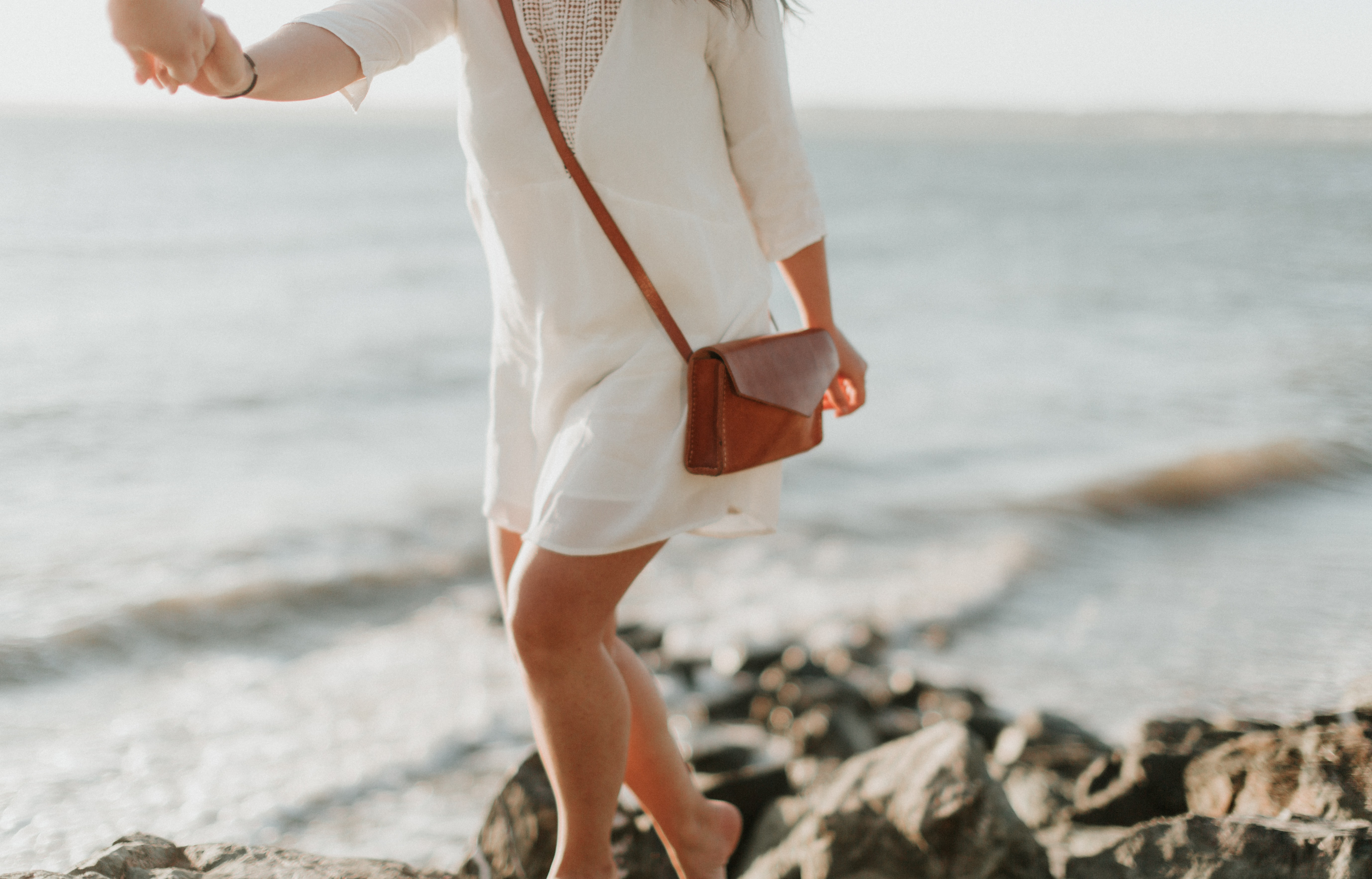 woman in white dress and brown leather sling bag walking on cliff