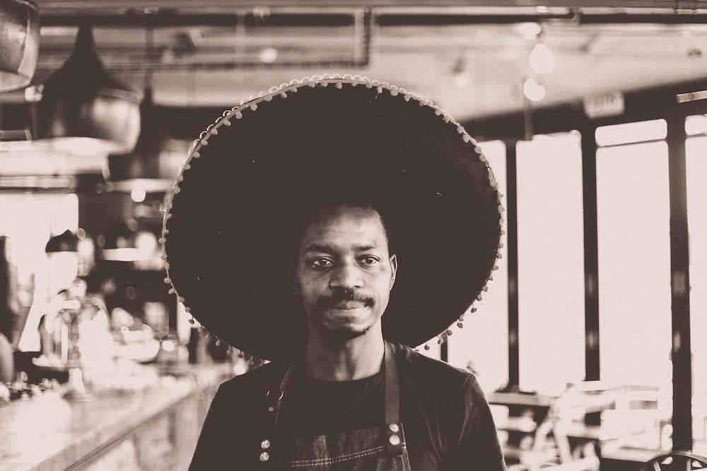 grayscale photo of man wearing sombrero