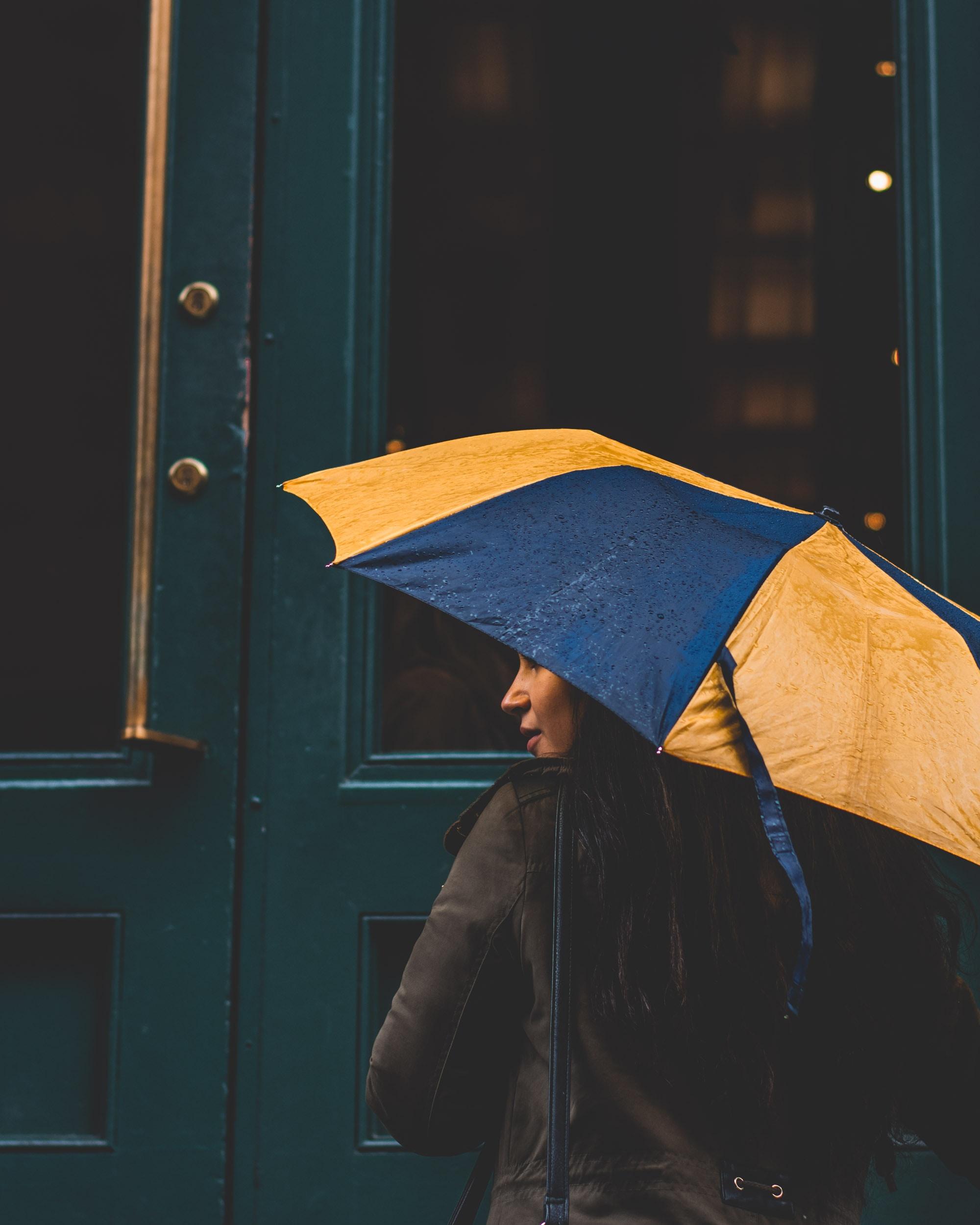 woman under yellow and blue umbrella beside green wooden door