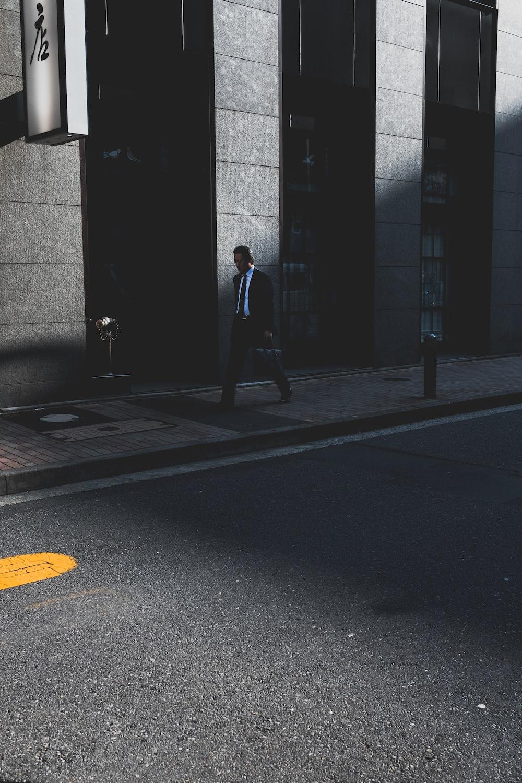 woman wearing suit walking near building during daytime
