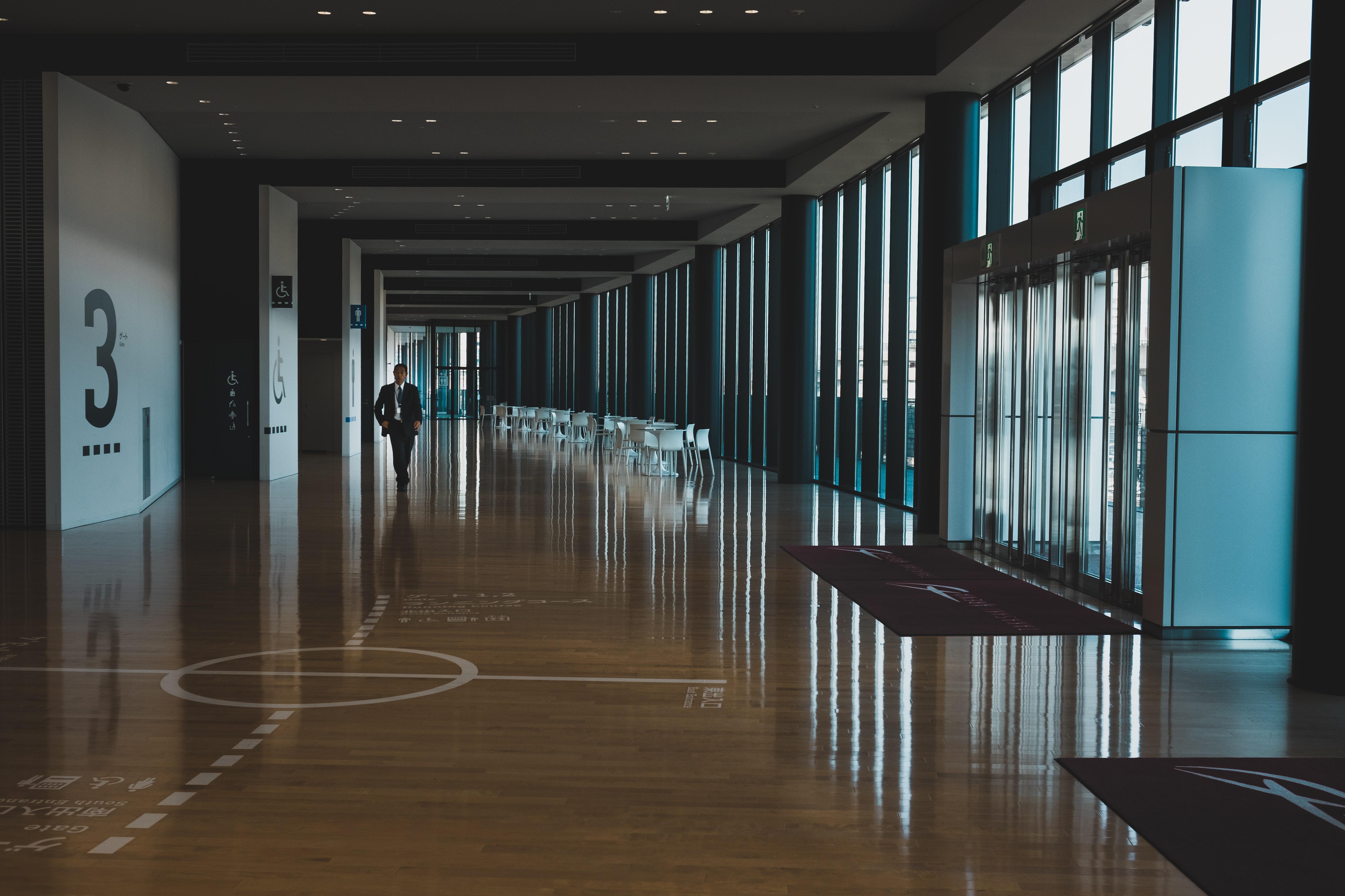 man in black formal suit jacket walking on hallway during daytime