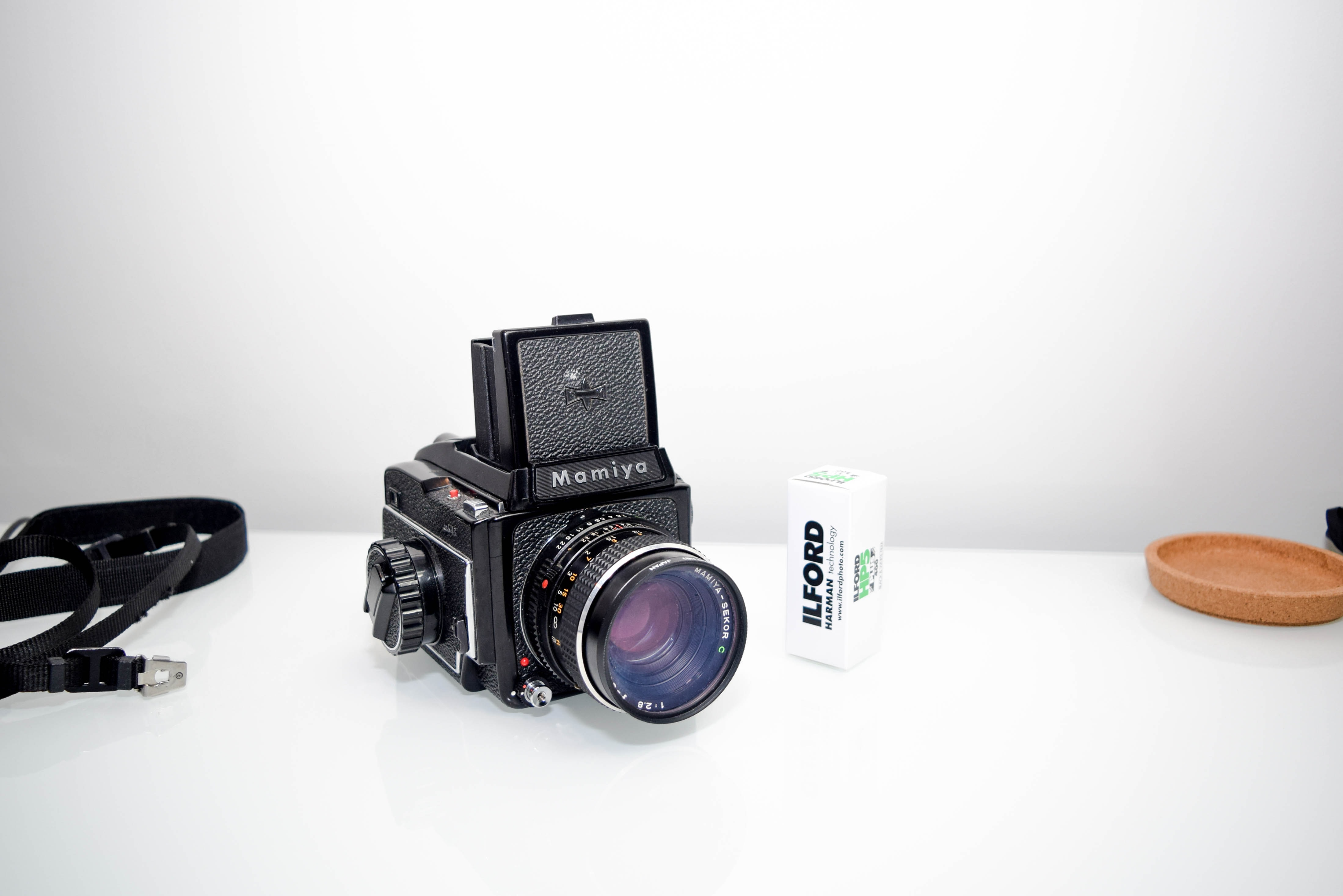 black Mamiya point-and-shoot camera in white table