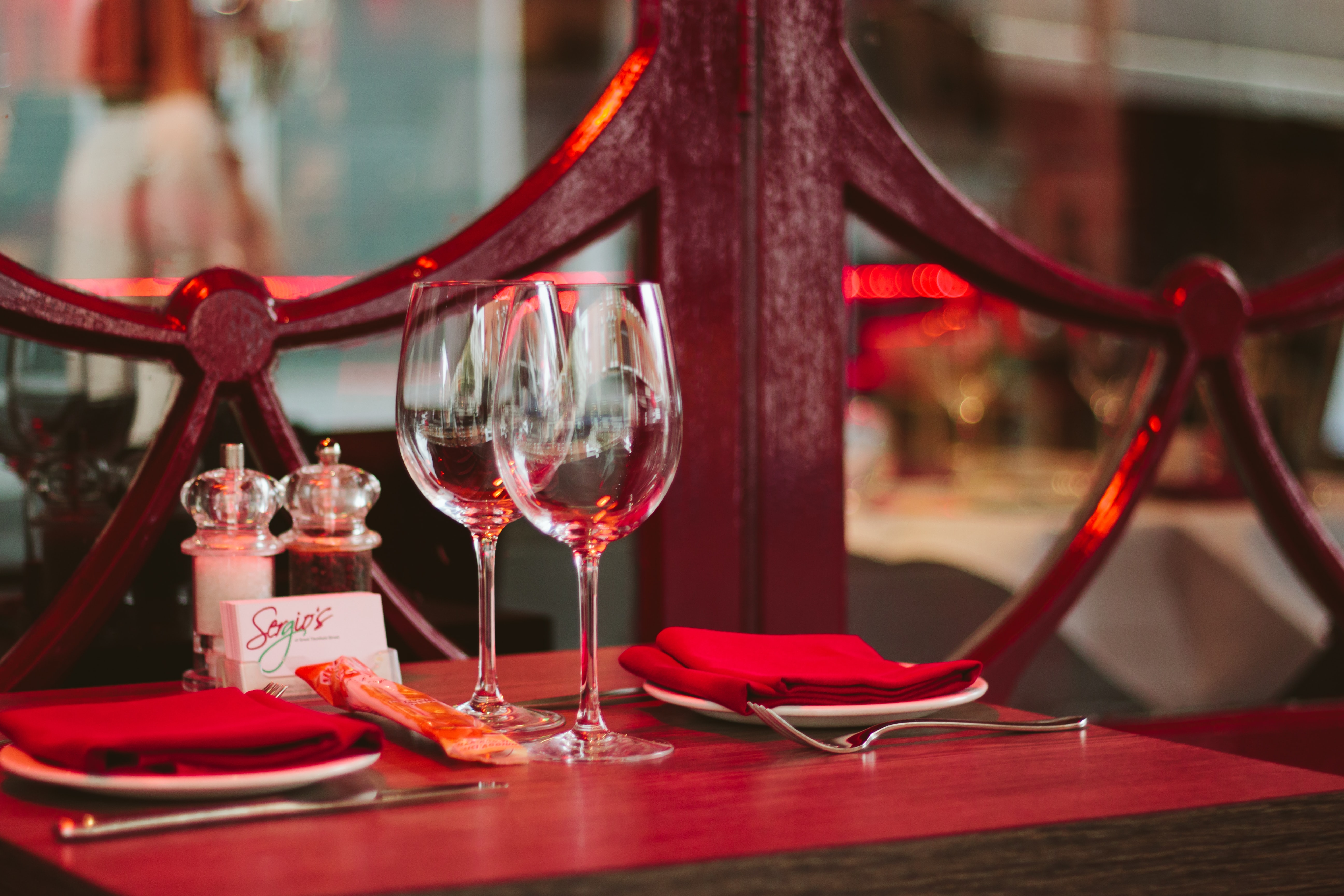 shallow focus photography of clear footed drinking glasses on table top beside white ceramic plates and red textiles