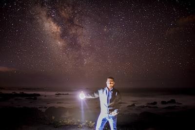 man holding flashlight illuminated teams background