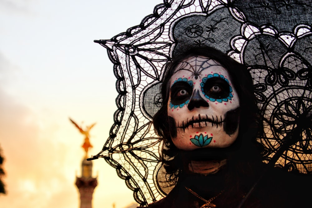 person with skull face paint and umbrella