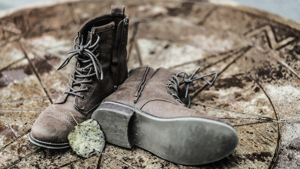 pair of brown side-zip lace-up boots on brown ground