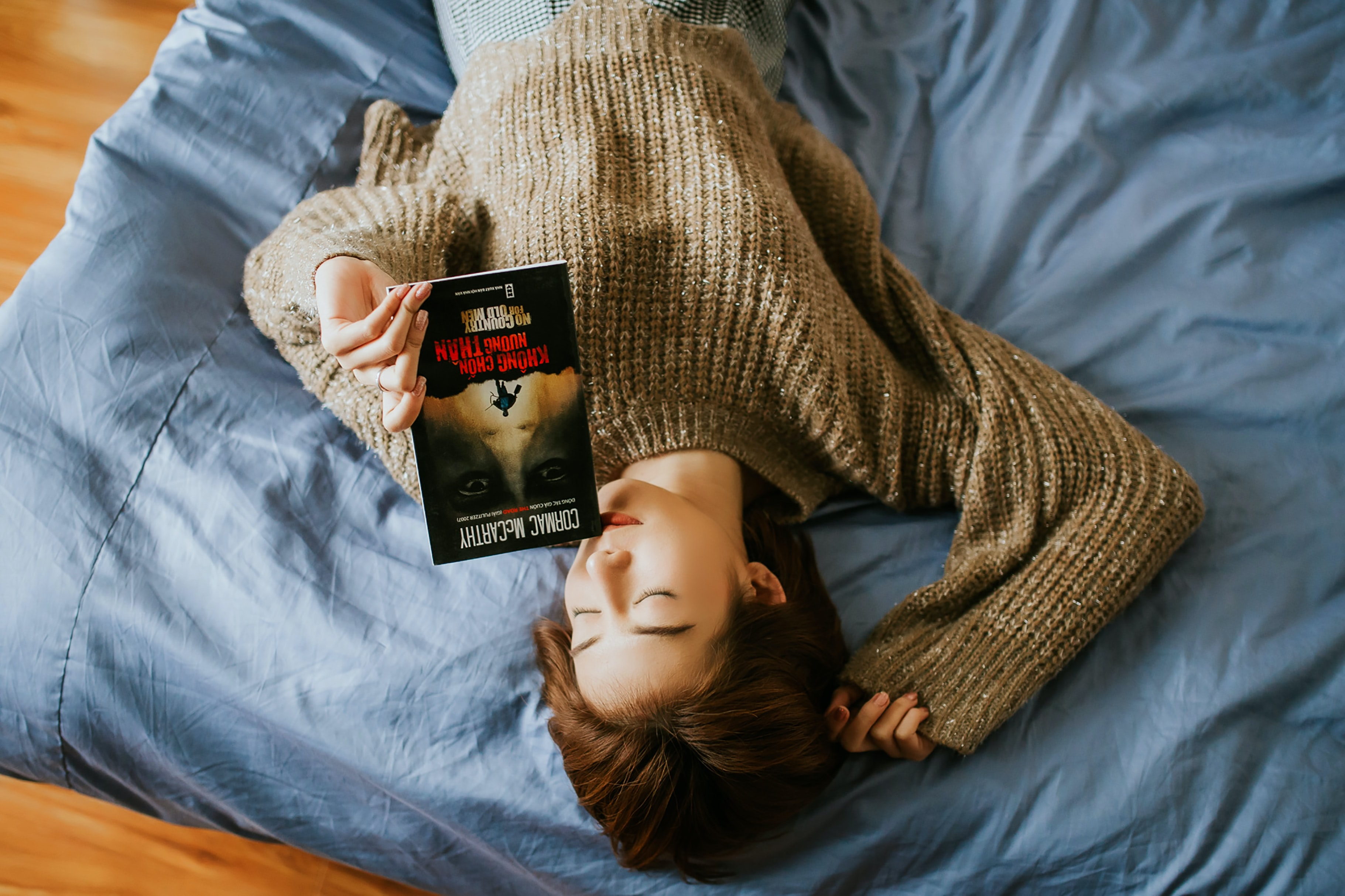 woman in sweater holding book while lying on bed