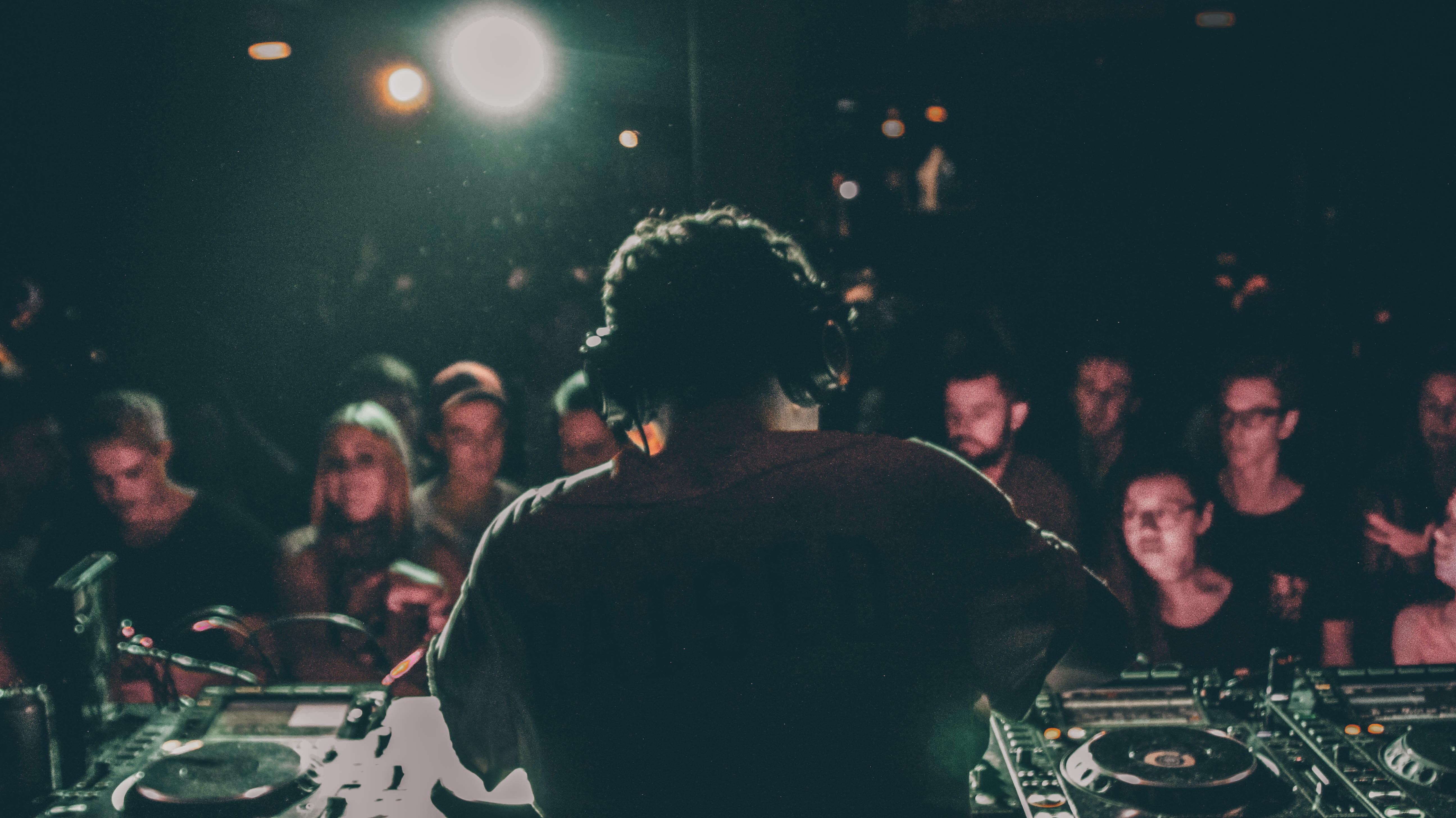 man in grey shirt operating black DJ turntable inside room