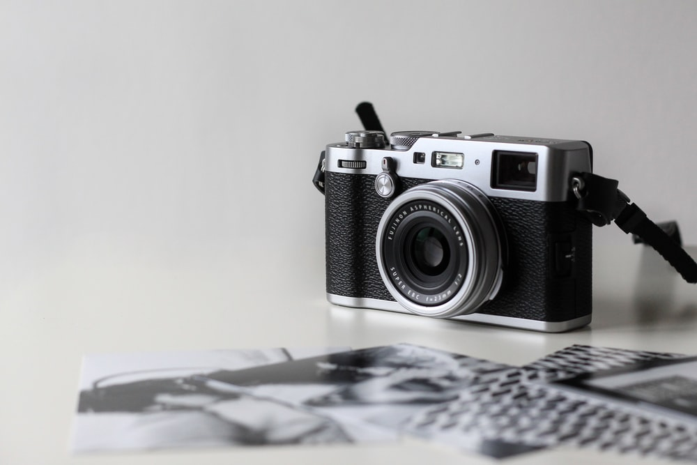 black and gray film camera near printed photos