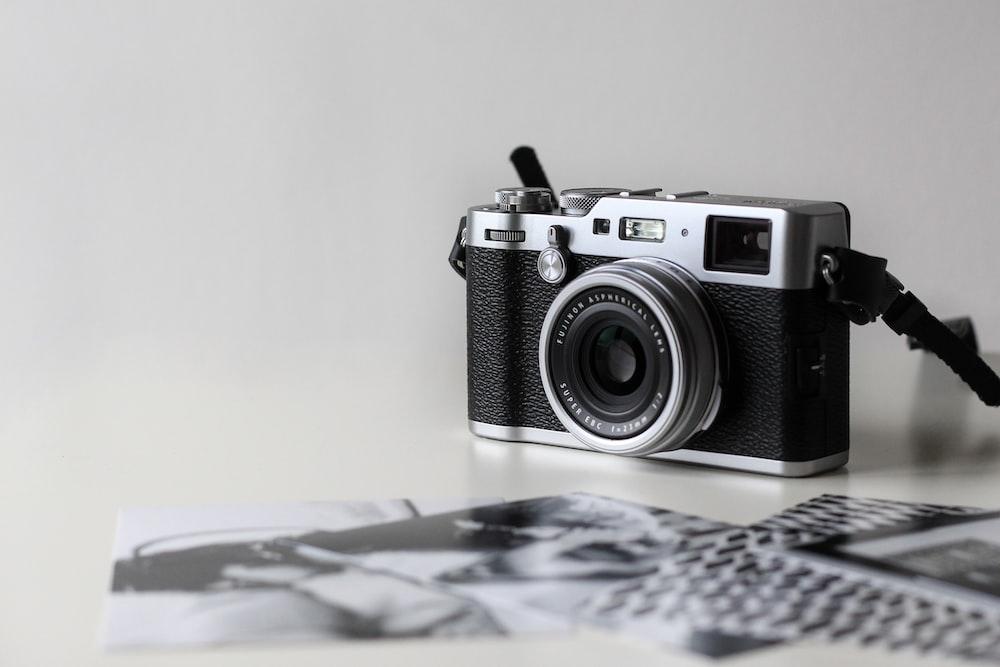 black and gray film camera near printed photos